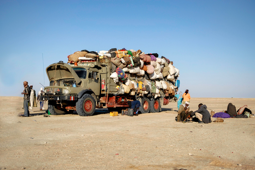 Mondou, Chad - December 8, 2012: The picture was took in the desert of Chad during a morning time, we can see a group of immigrant traveling to another country, they are close to a border, when the truck full of goods break down. December 2012